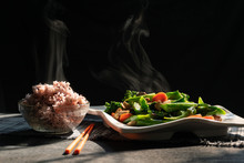 Steam From Hot-blanched Vegetables In Dish And Riceberry In A Cup On Wood Table With Morning Sun Light, Kale,Mushrooms And Carrots Contain Vitamins And Fiber With Good Health Benefits, Healthy Eating.
