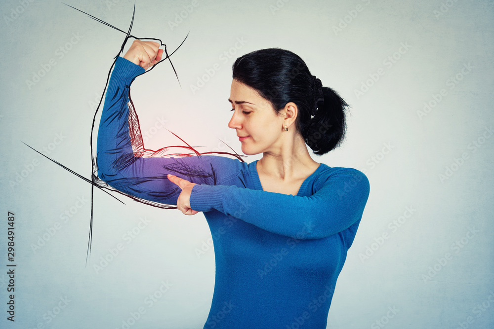 Fototapeta Confident and determined woman flexing muscles imagine has a powerful arm with big biceps. Girl showing her strength, positive face expression. Personal development and motivation concept.