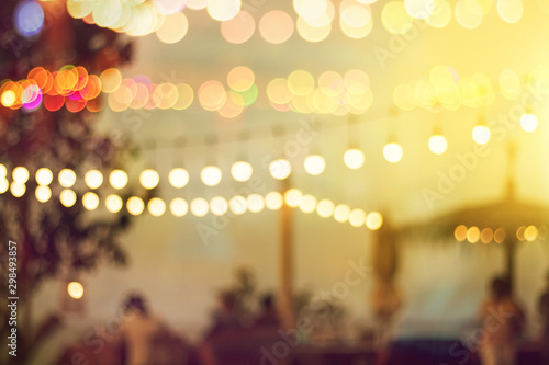 blurred bokeh light on sunset with yellow string lights decor in beach restauran Fototapet
