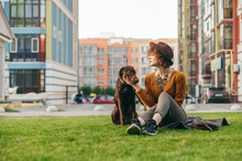 Portrait Of A Stylish Girl In A Hat Sits With A Beautiful Brown Dog On The Lawn Against The Backdrop Of A Modern Apartment Building, Looks At The Puppy And Strokes. Vacation With Your Pet.