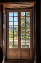 Wooden Carved And Glazed Doors Leading From Old House Into Garden With Sunlight