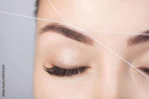 The make-up artist plucks eyebrows with a thread close-up Fototapet