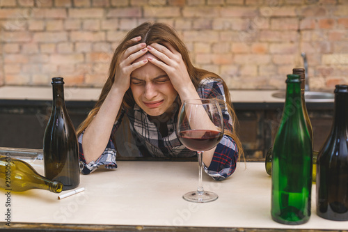 Valokuva Young sad and wasted alcoholic woman sitting at kitchen couch drinking red wine, completely drunk looking depressed lonely and suffering hangover in alcoholism and alcohol abuse