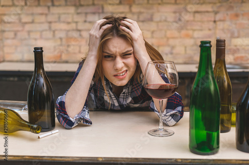 Vászonkép Young sad and wasted alcoholic woman sitting at kitchen couch drinking red wine, completely drunk looking depressed lonely and suffering hangover in alcoholism and alcohol abuse