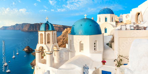 Staande foto Santorini Local church with blue cupola in Oia village, Santorini island, Greece. Panoramic image with Oia skyline, volcanic caldera and blue sea