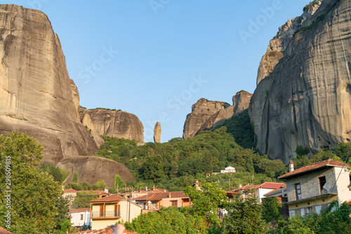 Valokuva  Houses and church in foothills among trees below towering rocks and pinnacles at Meteora