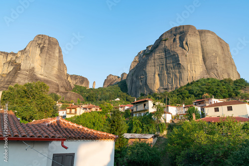 Houses and church in foothills among trees in valley below towering converging r Fototapete
