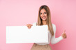 Leinwanddruck Bild - Young blonde woman over isolated pink background holding an empty white placard for insert a concept