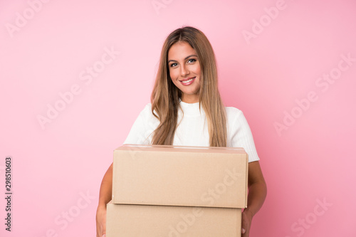 Photo Young blonde woman over isolated pink background holding a box to move it to ano