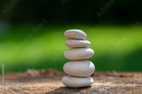 Photo Stands Zen White stones cairn, poise light pebbles on wooden stump in front of green natural background, zen like, harmony and balance