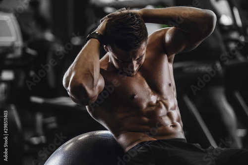 Handsome strong athletic men pumping up muscles workout fitness and bodybuilding concept background - muscular bodybuilder fitness men doing abs exercises in gym naked torso Canvas Print