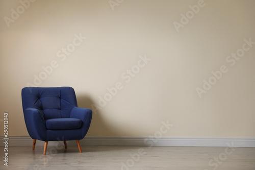 Photo Stylish comfortable armchair near light wall in empty room