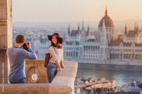Photo Young couple take pictures of each other on the view point from Fisherman Bastion in Budapest on sunrise