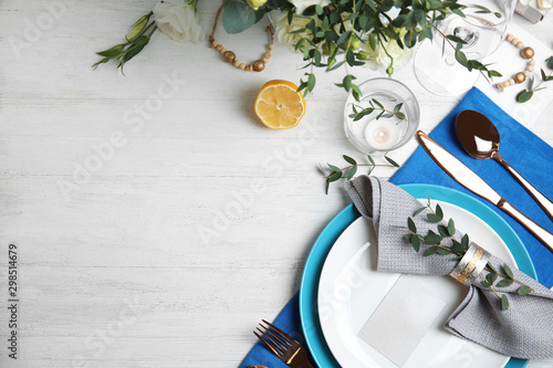 Elegant festive table setting on white wooden background, flat lay. Space for text