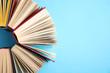 Leinwanddruck Bild - Hardcover books on light blue background, flat lay. Space for text