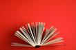 Leinwanddruck Bild - Hardcover book on red background, top view