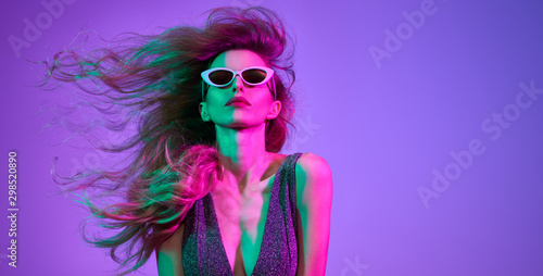 Obraz Fashionable glamour woman with Trendy wavy neon light hairstyle. Party night club vibes, gel filter. Excited shapely girl dance. Bright pink green lighting. Art fashion creative neon color. - fototapety do salonu