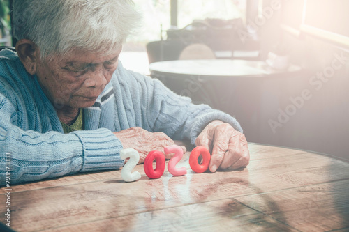 Old person hands holding number 2020 on wood table Canvas-taulu