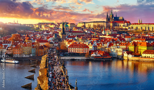 Obraz Panoramic view above at Charles Bridge Prague Castle and river Vltava Prague Czech Republic. Picturesque landscape with sunset old town houses with red tegular roofs and broach tower. - fototapety do salonu