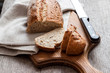 Leinwandbild Motiv Loaf of whole wheat bread with slices on wooden board on kitchen table