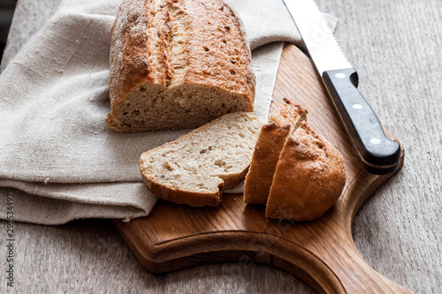 Tuinposter Brood Loaf of whole wheat bread with slices on wooden board on kitchen table