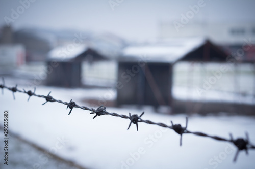 barbed wire closeup with detention camp in background Canvas-taulu
