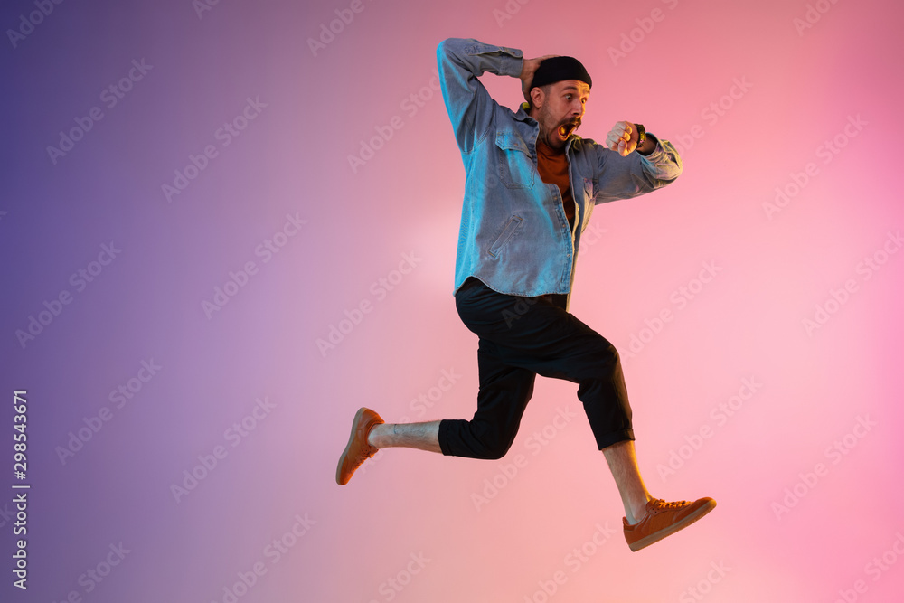 Fototapety, obrazy: Full length portrait of happy jumping man wearing casual clothes in neon light isolated on gradient background. Emotions, ad concept. Expressive hurrying up, late for work or sale, shopping.