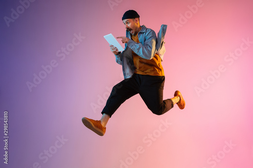 Photo Full length portrait of happy jumping man wearing casual clothes in neon light isolated on gradient background