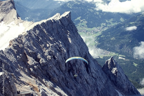 Person paragliding from the top of Zugspitze Mountain with jagged cliffs in background
