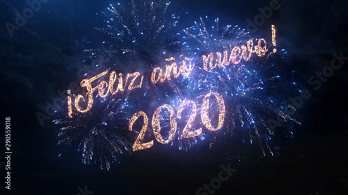 2020 Happy New Year greeting text in Spanish with particles and sparks on black night sky with colored fireworks on background, beautiful typography magic design Canvas Print