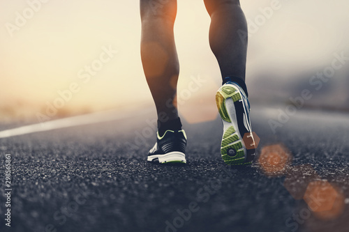 fototapeta na drzwi i meble close up sport shoes of a runner on road for fitness healthy lifestyle.