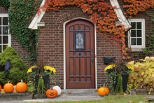 Front Door Of House With Halloween Decorations And Pumpkins