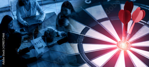 Business Target Goal For Success Strategy Concept - Red dart arrow hitting center goal on the dart board with business people working in background showing precision and success of business target Wallpaper Mural