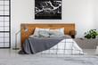 canvas print picture - Black map on white wall above wooden headboard in simple bedroom interior