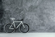 White And Black Bike On Empty Grey Concrete Wall, Real Photo With Copy Space