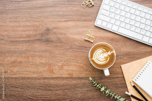 Obraz na plátně  Wood minimalist office desk table with computer keyboard, cup of cafe latte coffee and supplies