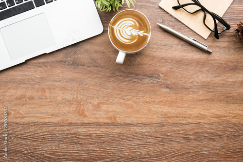 Wood minimalist office desk table with laptop computer, cup of cafe lattee coffee and office supplies. Top view with copy space, flat lay, minimal style.