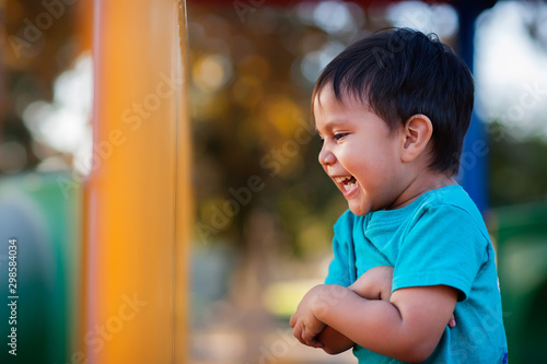 Fotografía  Young boy laughing out loud and holding his arms together while playing in a jungle gym