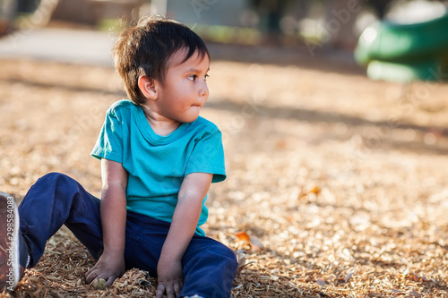 Valokuvatapetti Latino boy with dirty hands from playing with woodchips from a playground all by himself and looking away