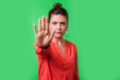 canvas print picture - Stop, no! Portrait of angry or worried young woman with bun hairstyle, big earrings and in red blouse frowning gesturing caution to camera, prohibition. indoor studio shot isolated on green background