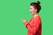 canvas print picture - Hey you! Side view portrait of amazed girl with bun hairstyle, big earrings and in red blouse pointing finger to the left, looking with astonishment. indoor studio shot isolated on green background