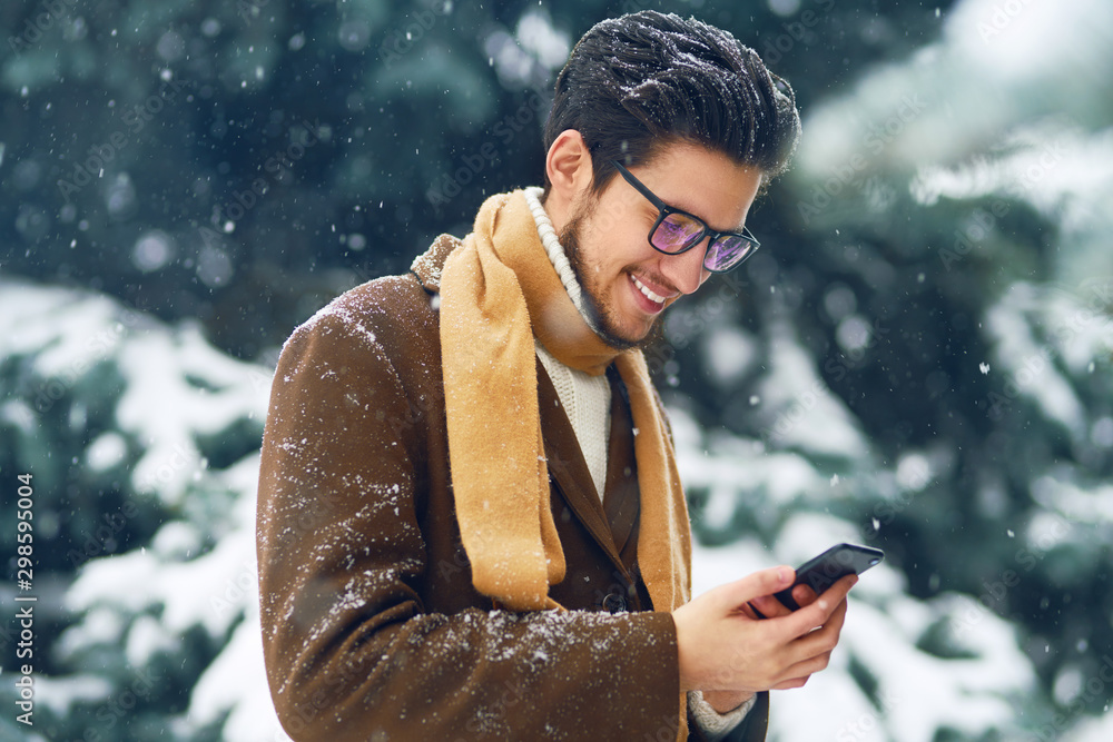 Fototapety, obrazy: Young man in a coat on the street with a phone. Smiling young man having fun outdoors. Businessman uses a phone.  Man enjoy a winter. Dressed in a coat, sweater and scarf. Winter concept. Snowfall.