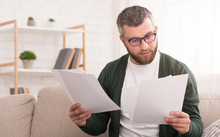 Interested Serious Man Holding Papers With Both Hands, Reading It
