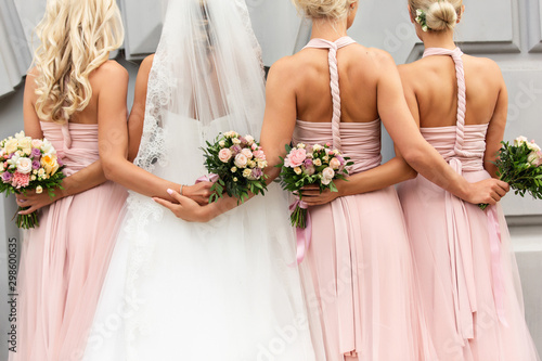 Fotomural  Bride and bridesmaids in pink dresses hugs and posing with bouquets at wedding day