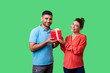 canvas print picture - Gift for family. Portrait of happy couple in casual wear standing, holding box with present and looking at camera together, enjoying holiday surprise. isolated on green background, indoor studio shot