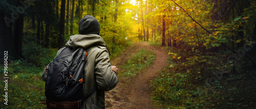 A man with backpack walks in the amazing autumn forest Canvas Print