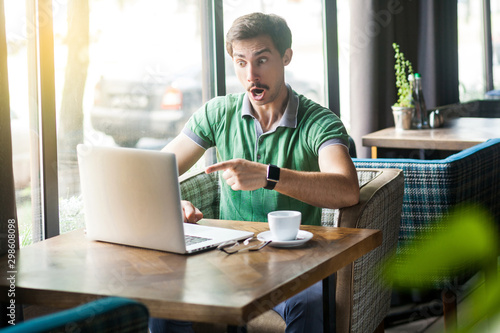 Young shocked businessman in green t-shirt sitting, working, looking and pointing at laptop display with amazed unbelievable face Fototapet