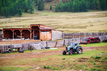 Old Wheeled Tractor Near The Fence Of A Livestock Farm. Russia, Mountain Altai, Ongudaysky District, The Village Of Bichiktu-Boom