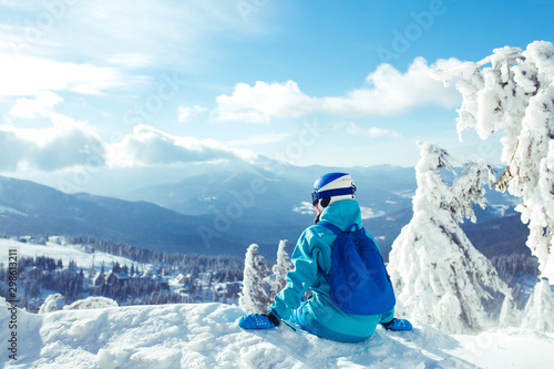 Foto auf Gartenposter Blau A young girl enjoys beauty of winter landscape. A beautiful girl in winter clothes, a blue helmet and jacket is having a great time in the mountains. Concept of travel, leisure, freedom, sport, nature