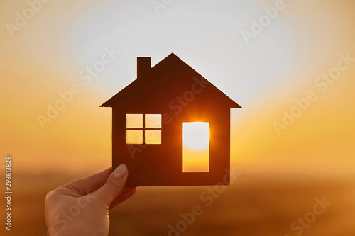 Woman hand holds wooden house against the sun